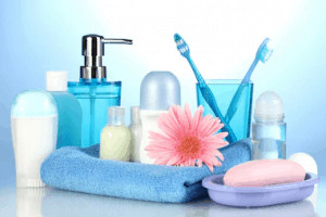 Assortment of bathroom supplies and pink flower.