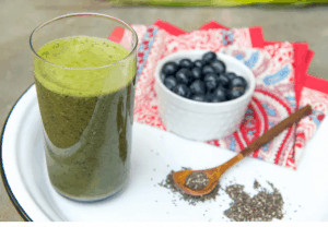 Glass of green juice on plate with berries and chia seeds.