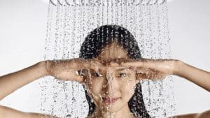 Woman under running shower head with her hands shading her eyes.
