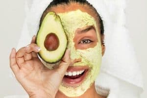 Girl with face mask holding avocado.