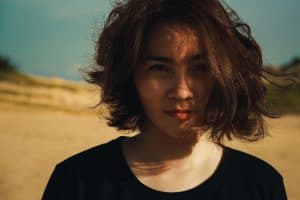 Woman with short hair smirking is desert.