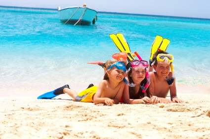 Three children wearing snorkeling gear on the beach.