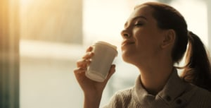 Woman closign her eyes and holding a cup.