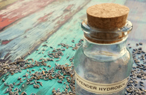 Small bottle labeled 'lavender hydrosol' surrounded by seeds.