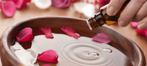 Small brown bottle being poured in bowl of liquid filled with red petals.