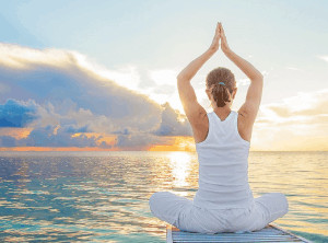 Woman with palms touching above head sitting crossed legged in front of ocean sunset.