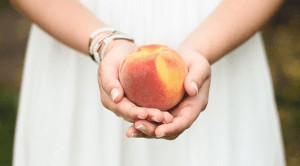 Woman holding apricot.