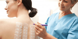 Woman getting a patch test on her back by doctor.