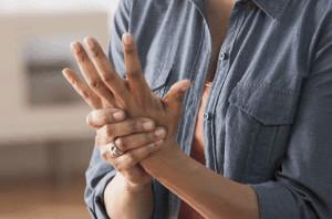 Woman massaging hand.