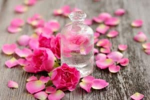 Small bottle of clear liquid surrounded by pink flowers.