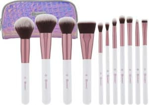 Assorted makeup brushes in a row in front of a purple makeup bag.