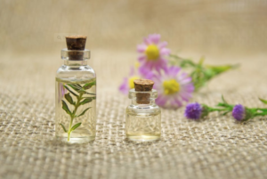 Two small bottles of oil with flowers in background.