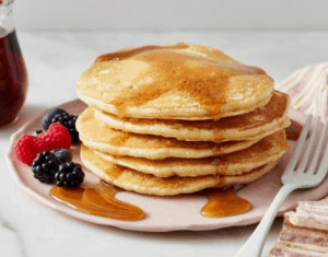Pancakes on plate with maple syrup and berries.