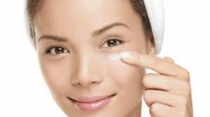 Woman putting lotion under eye.