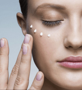 Woman dabbing row of lotion drops on her face.