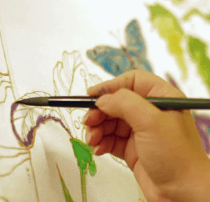 Hand holding pen creating art on canvas.