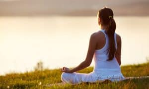 woman in all white meditating on the grass by a body of water