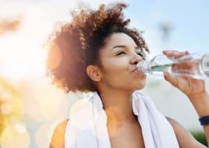 Woman runner drinking water.