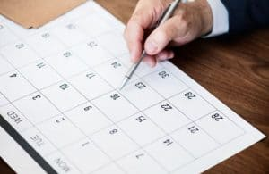 Hand holding pen pointing to date on calendar.