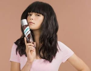 Brunette woman holding a can of batiste dry shampoo.