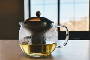Tea pot on table in front of window.