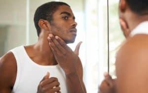 African american man applying aftershave looking in mirror.