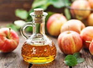 Apples and bottle of apple cider vinegar.