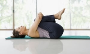 Woman doing knees to chest pose.
