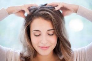 Woman massaging her own scalp.