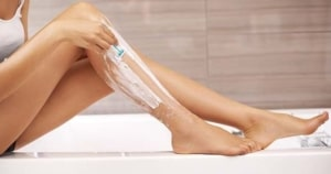 Woman shaving her smooth legs.