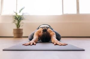 Woman laying on a mat doing yoga