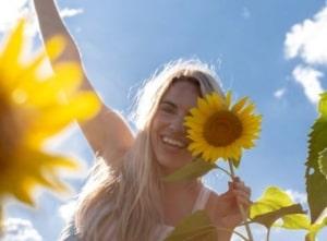 Girl holding sunflower to face.