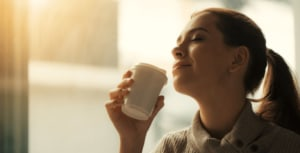 Woman with eyes closed holding a hot beverage.