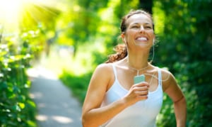 Woman jogging while smiling.