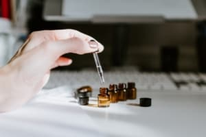 Hand dripping oil into tiny vials.