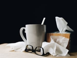 Cup of tea, tissue box, and glasses on table.