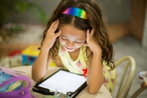 Girl looking at tablet at the kitchen table.