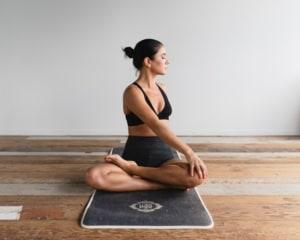 Woman doing spine twisting yoga pose.