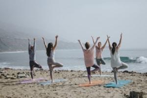 Women doing yoga on the beach.