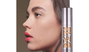 Side profile of woman next to bottle of urban decay all nighter foundation.