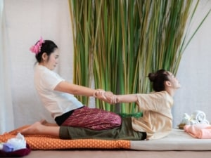 Woman receiving a Thai massage with stretches.