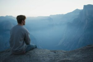 Man sitting on a cliffside looking out to the foggy skywearing jeans and a sweatshirt
